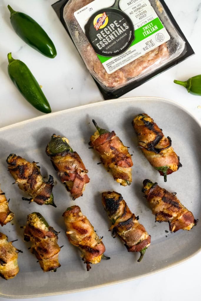 Grilled stuffed jalapeños with sausage and cheese bring the heat, the sweet, and the smokiness for a flavor bomb appetizer that's perfect for your next grilling night, or your next tailgate!