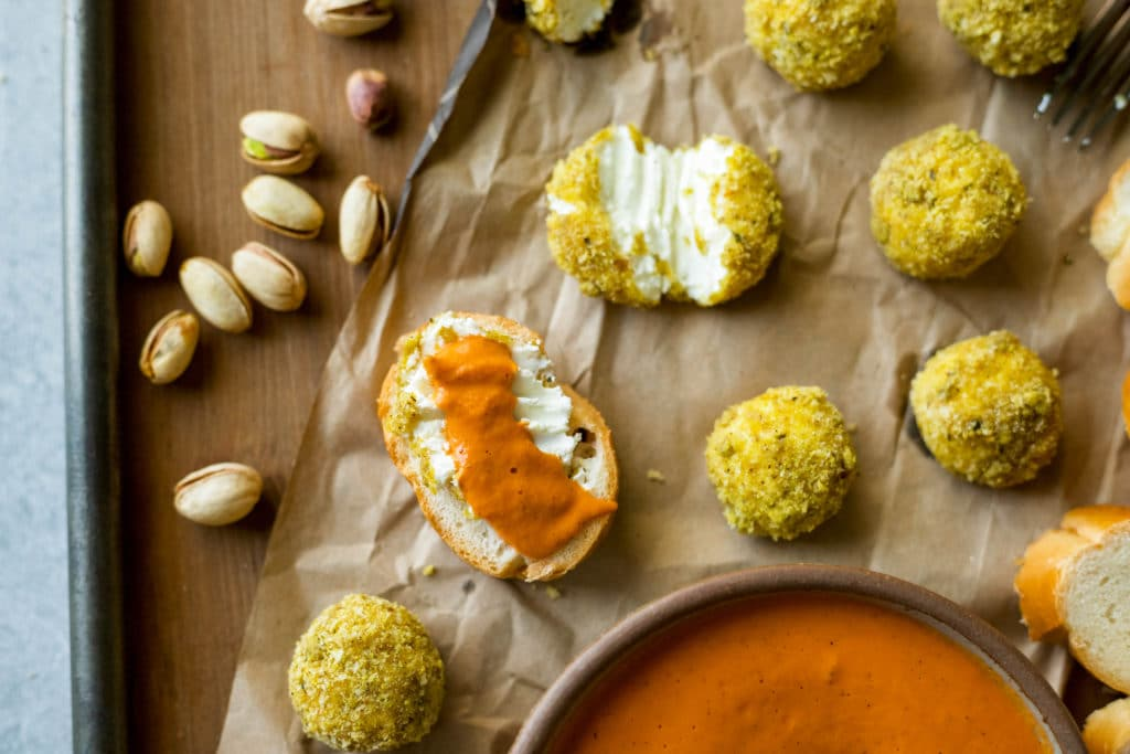 creamy goat cheese coated in crunchy pistachios and bread crumbs, then baked and served with a fire roasted tomato and red pepper sauce | a flavor journal food blog