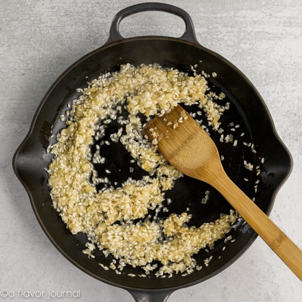 A cast iron skillet with olive oil, onions, garlic, arborio rice, and chicken stock cooking in it.