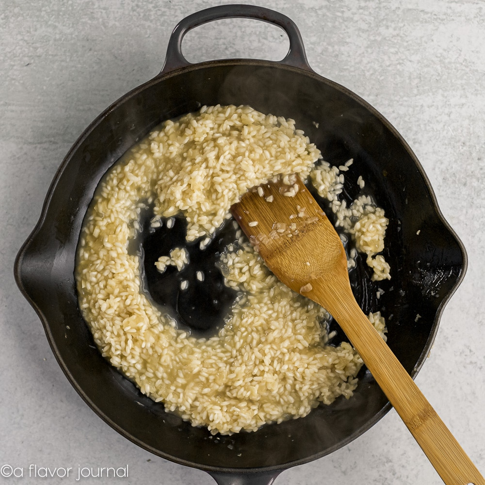 A cast iron skillet with olive oil, onions, garlic, arborio rice, and chicken stock cooking in it to make parmesan risotto.