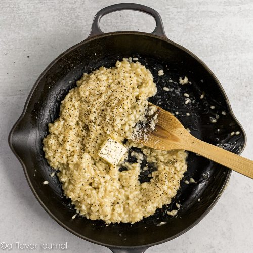 A cast iron skillet with parmesan risotto cooking in it, and a slab of butter in the middle.