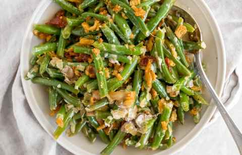 A top down view of a ceramic plate full of fresh green bean casserole, with a spoon tucked into the casserole off to the right hand side.