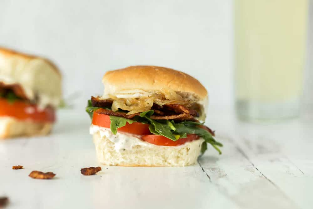 Mini BLT sandwiches with caramelized onions, arugula, black pepper mayonnaise and juicy, ripe tomatoes. This recipes makes six, but can be multiplied to feed a crowd!