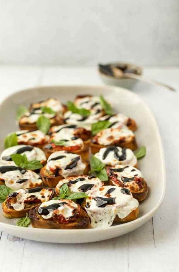 Oven baked crostini layered with pesto, oven-roasted tomatoes, melted mozzarella, balsamic drizzle, and fresh basil leaves.