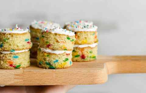 Mini Funfetti cakes stacked with vanilla frosting, sitting on a small cutting board together and being held in the air.