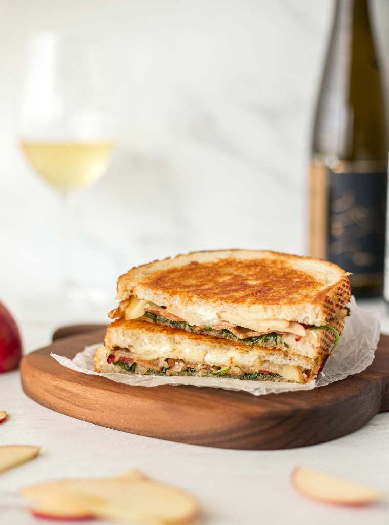 A grilled cheese sandwich on an apple shaped cutting board with a bottle of Riesling and a glass of wine in the background
