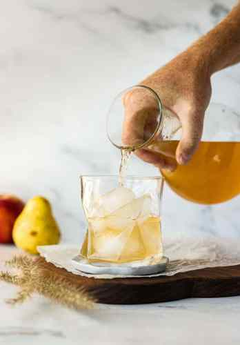 Baked pear and apple sangria being poured from a small carafe into a glass filled with ice.