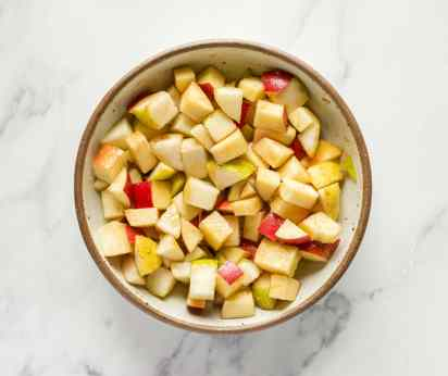 A bowl of apples and pears tossed with brown sugar for a baked pear and apple sangria.