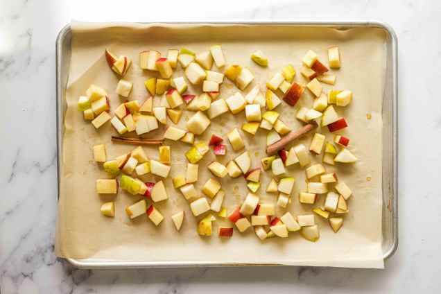 Chopped apples and pears tossed with brown sugar and cinnamon sticks on a sheet pan lined with parchment paper.