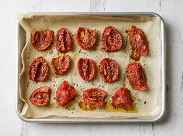 A rimmed baking sheet lined with parchment paper full of roasted tomatoes.