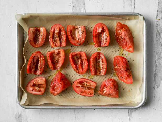 A rimmed baking sheet lined with parchment paper full of fresh, ripe tomatoes that have been cut in half.
