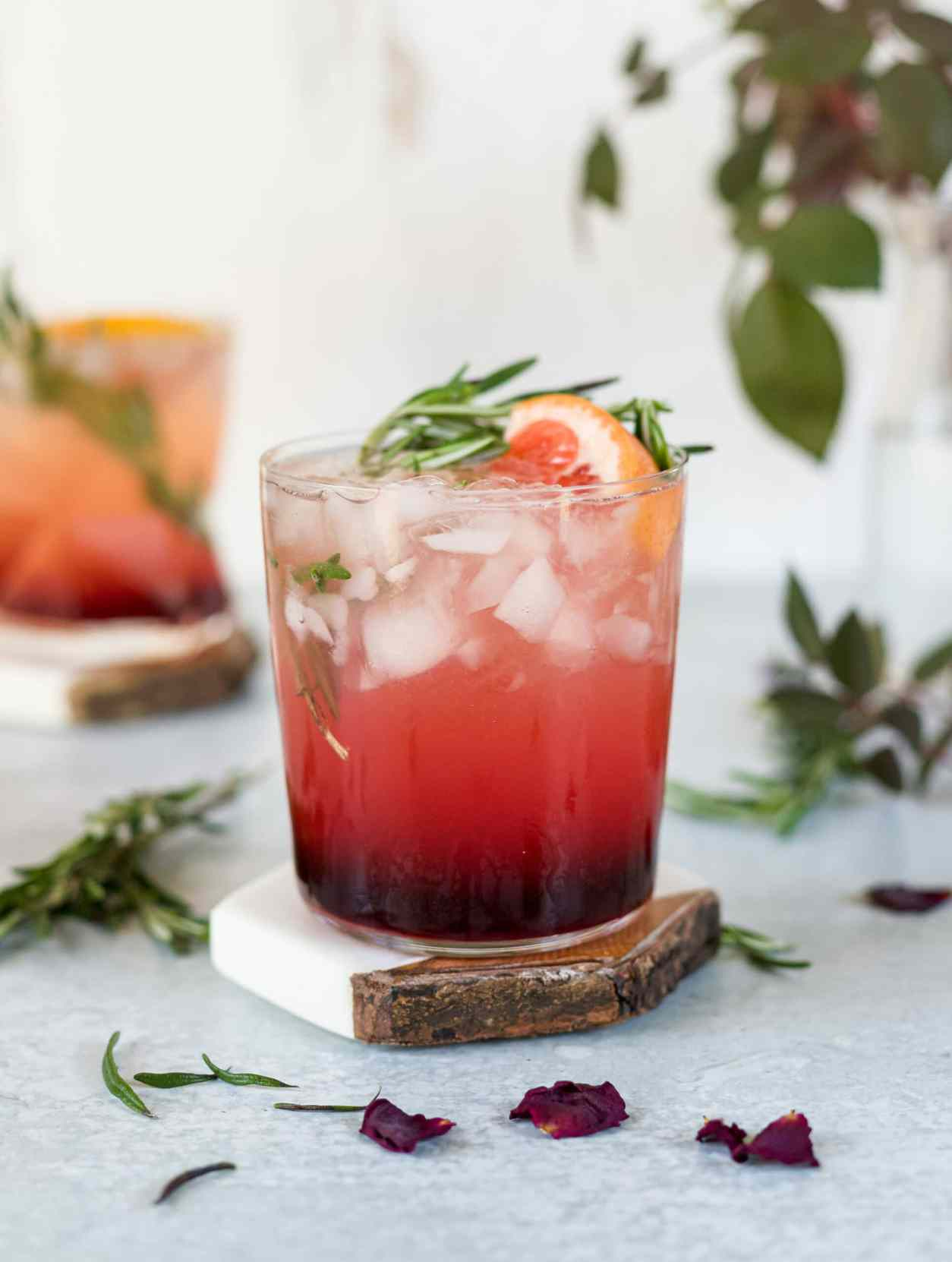 A cocktail glass filled with a pomegranate cocktail and garnished with grapefruit and rosemary.