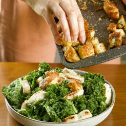An action shot of toasted croissant croutons being placed on top of a chicken kale salad.