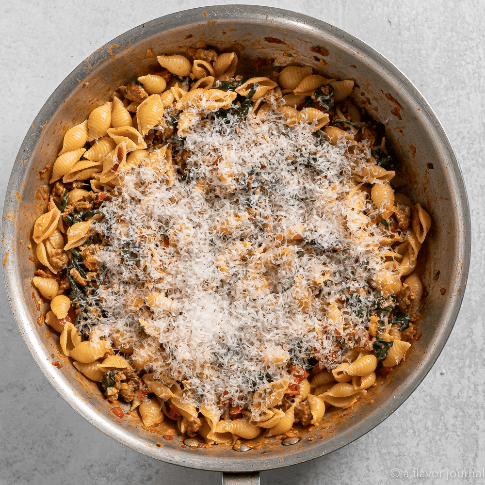 Process shot of cooking chorizo and tomato pasta with fresh spinach and parmesan