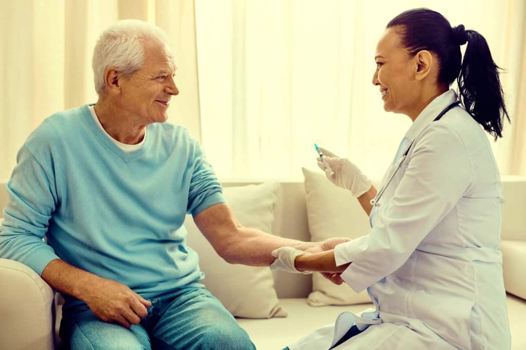 Image of nurse giving older patient a shot