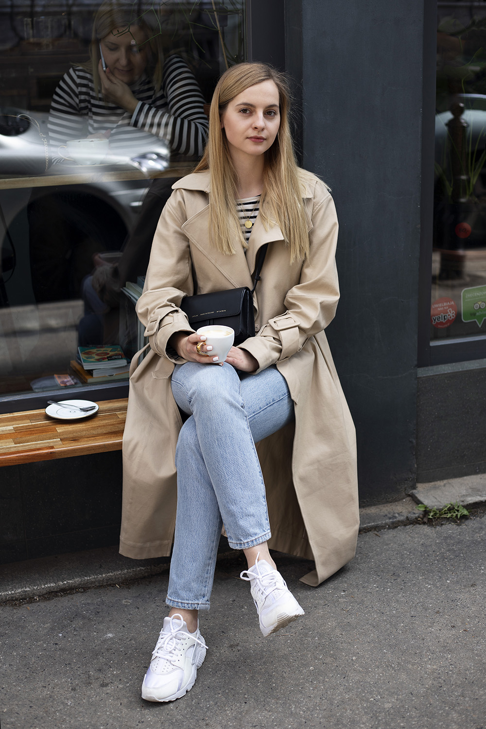 Girl drinking coffee in beige H&M trench and blue jeans