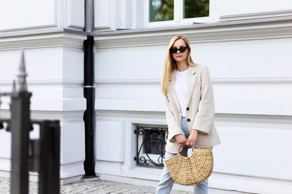 Girl in linen H&M jacket straw basket and cat eye sunglasses