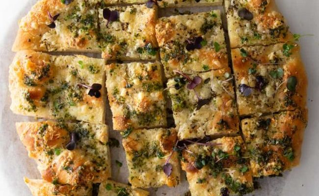 Fontina pizza squares with pesto herb oil and micro greens