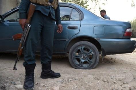 アフガニスタンの首都カブールで、タイヤの空気を抜いた車の横に立つ警察官(2016年8月23日撮影)。(c)AFP/WAKIL KOHSAR