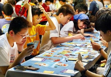 米国で行われる「ポケモンワールドチャンピオンシップス」の出場権を懸け、東京都内で開かれたカードゲームの大会に参加した子どもたち(2002年7月27日撮影、資料写真)。(c)AFP/YOSHIKAZU TSUNO