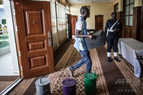 ガンビア・セレクンダにあるホテルの会見場に運び込まれた投票用のドラム缶と選挙関連資料を運ぶ男性(2016年11月28日撮影)。(c)AFP/Marco LONGARI