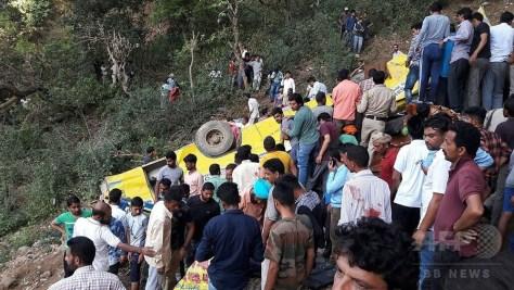 インド北部ヒマチャルプラデシュ州カングラ地区で、渓谷に転落したスクールバスの周囲に集まる人々(2018年4月9日撮影)。(c)AFP PHOTO