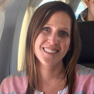 Woman smiling on a small plane while overcoming her fear of flying with Dr. Shulman.