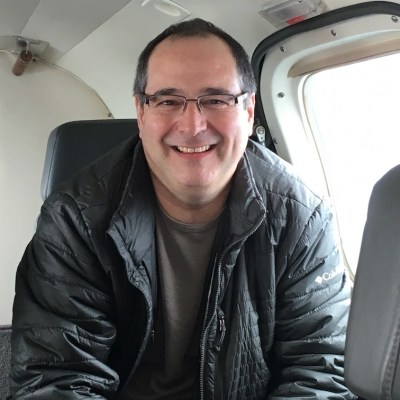Man, smiling broadly while sitting by the door on a small plane after taking Dr. Shulman's 'The Non Flyer' course.