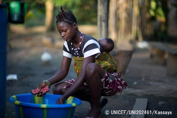 [NAME CHANGED] On 14 November 2015, Amina Kamara, 15, washes laundry with her son Ali, 6 months carried in a sling on her back at home, in Motonko Village, Ribbi Chiefdom, Moyamba District.