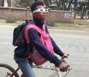 自転車を止めて太陽を見る少年