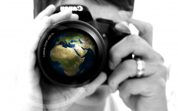 woman-camera-hand-lens-earth-globe-europe-africa