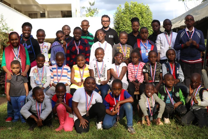 Group photo of all prize winners posing with tournament officials and schoolteachers