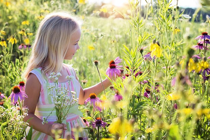 A kid picking a flower and feeling happy