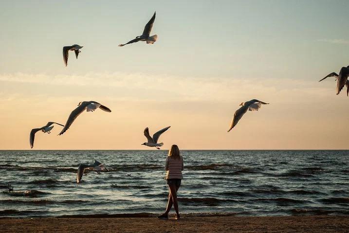 A woman at the beach feeling hopeful