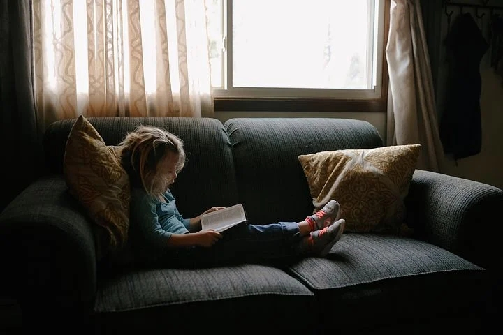 A kid spending time with God reading the Bible