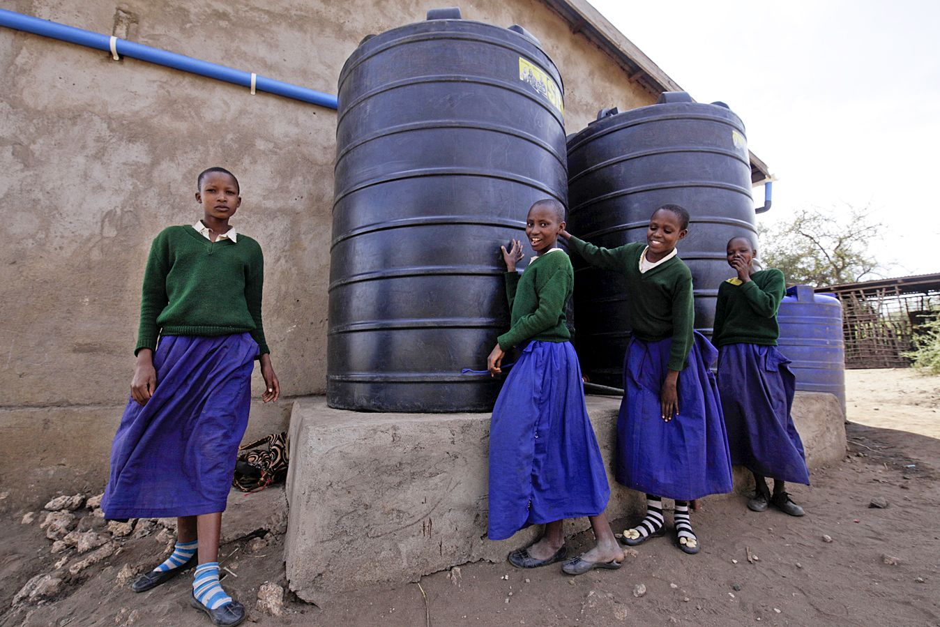Young Maasai girls stand by barrels of harvested rainwater.