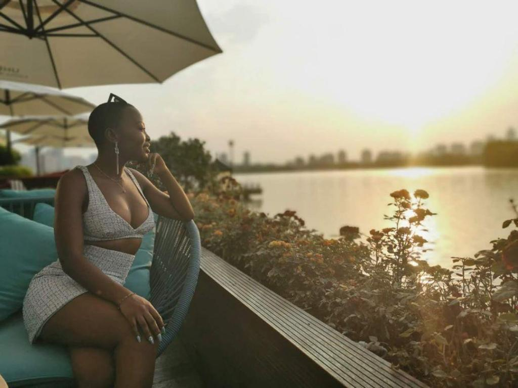 Khanya sittting near water with sunset