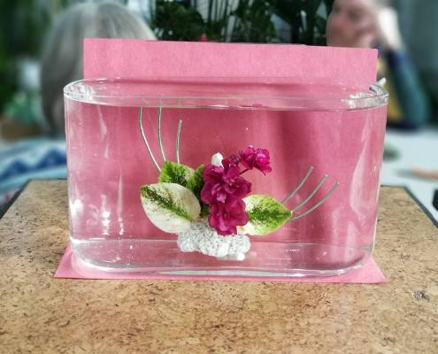 Underwater African violet arrangement using deep pink flowers and variegated leaves in front of a pink backdrop