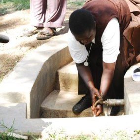ghana woman washing at well