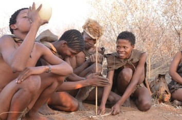 san-people-of-namibia-busy-in-firemaking-process-in-their-traditional-wear-photo-by-skimlet