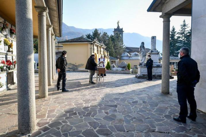 In Zogno, Lombardy, funeral directors and a priest are the only people present at a funeral of a corona victim.