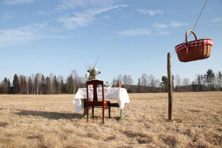 One table with a chair and basket of food via rope