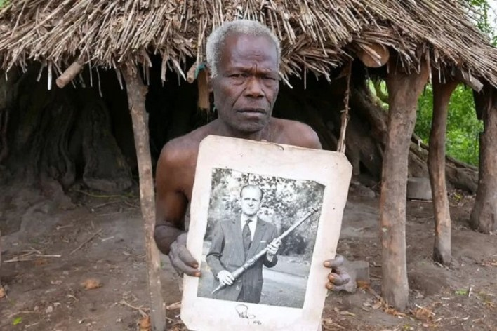 A resident of Tanna shows the photo of Prince Philip posing with the wooden stick the villagers made for him. (photo from 2017)