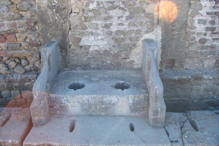 Roman toilet surrounded by sculptures of dolphins
