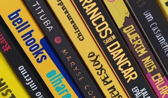 Pilha com vários livros escritos por pessoas negras. Eles possuem lombadas amarelas e pretas, e estão organizados de uma forma em que as cores vão se alternando.