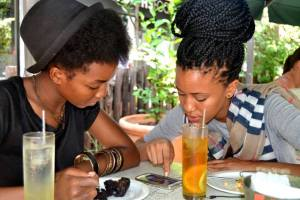 Mpho showing Boitshepo some of her artiwork for her cover song. Credits: The Empire BW Photography