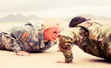 Two female Army Officers, playfully doing push-ups.