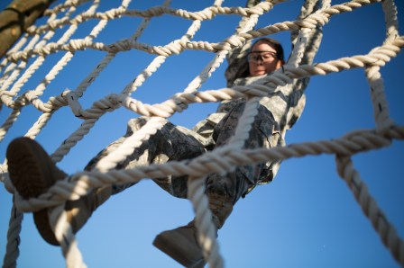 Female Soldier descending a high net at a confidence course