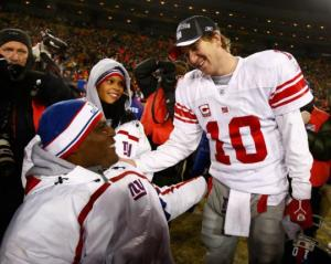 Eli Manning shares a moment with Lt. Col. Greg Gadson and his son after the Giants' NFC Championship win in Green Bay in January 2008. (Gett photo)
