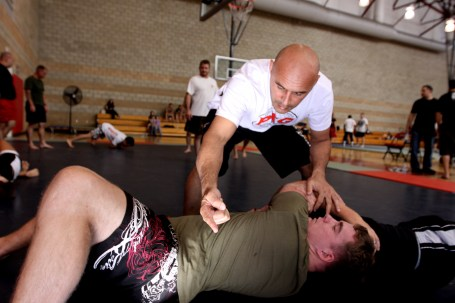 Tahi Burns, mixed martial arts instructor and fighter, critiques Sgt. John Hall, weapons technician, 1st Marine Division, on proper grappling techniques during a special MMA clinic for Camp Pendleton Marines at Paige Fieldhouse, Oct. 26. Lance Cpl. Damien Gutierrez/USMC